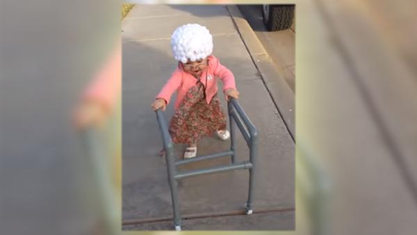 Flickan är utklädd till en gammal tant med rullator – titta bara när hon kommer gående
